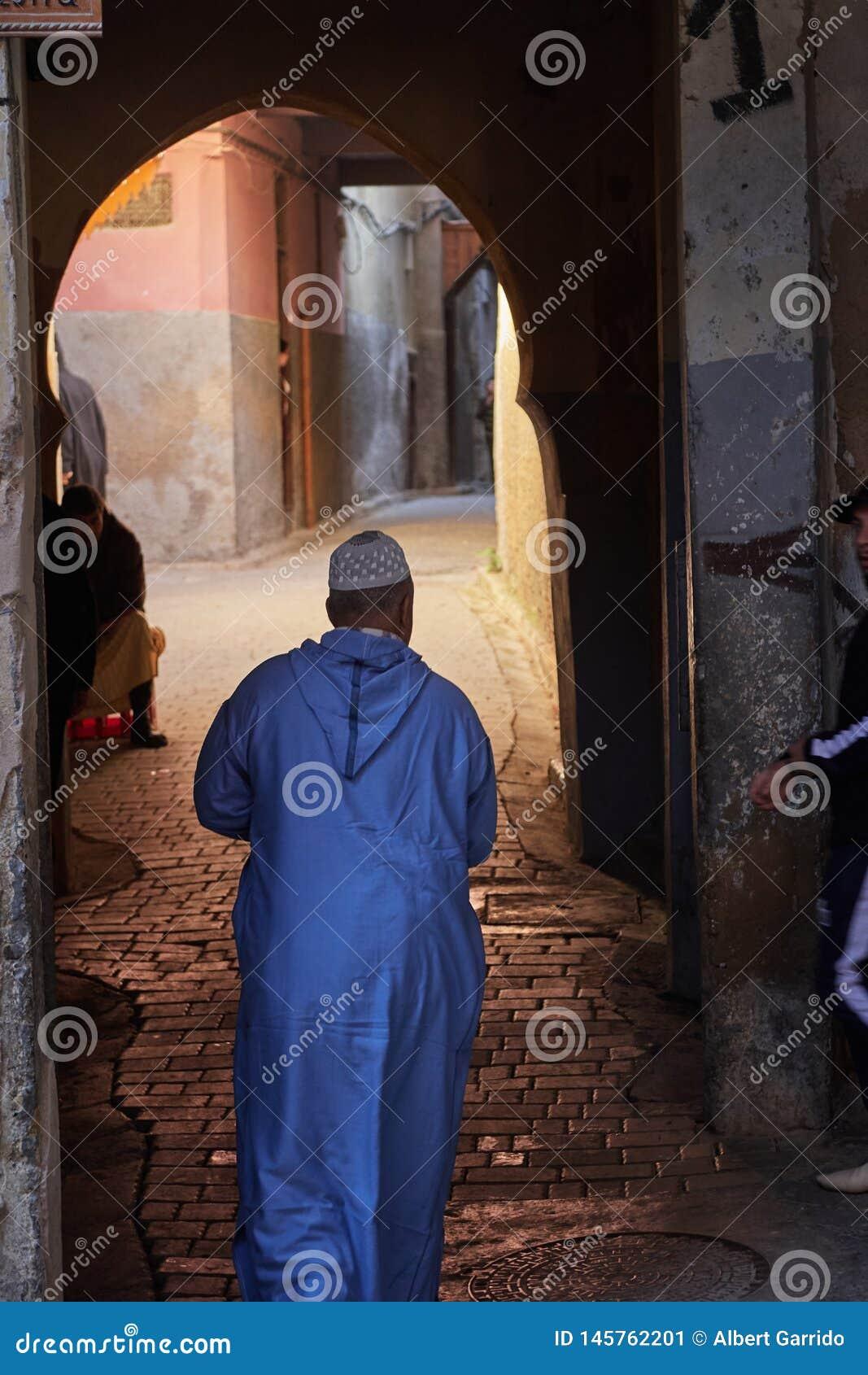 Fez Maroko, Grudzień, - 07 2018: Marokański starszy dżentelmen ubierał w błękicie, iść przez przejścia w Medina fez
