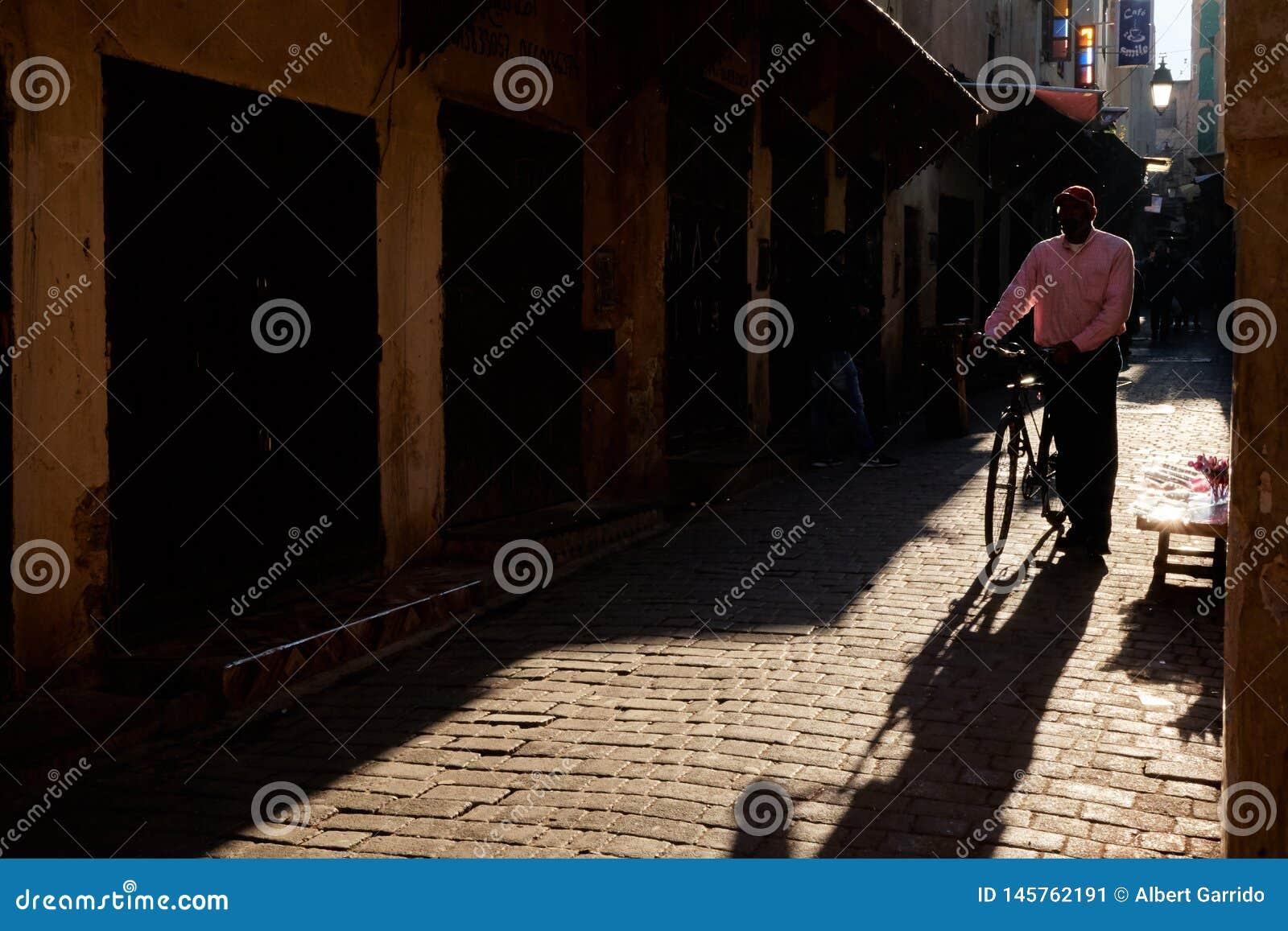 Fez, Marrocos - 7 de dezembro de 2018: Cavalheiro marroquino que anda abaixo de uma rua velha no medina do fez com uma bicicleta