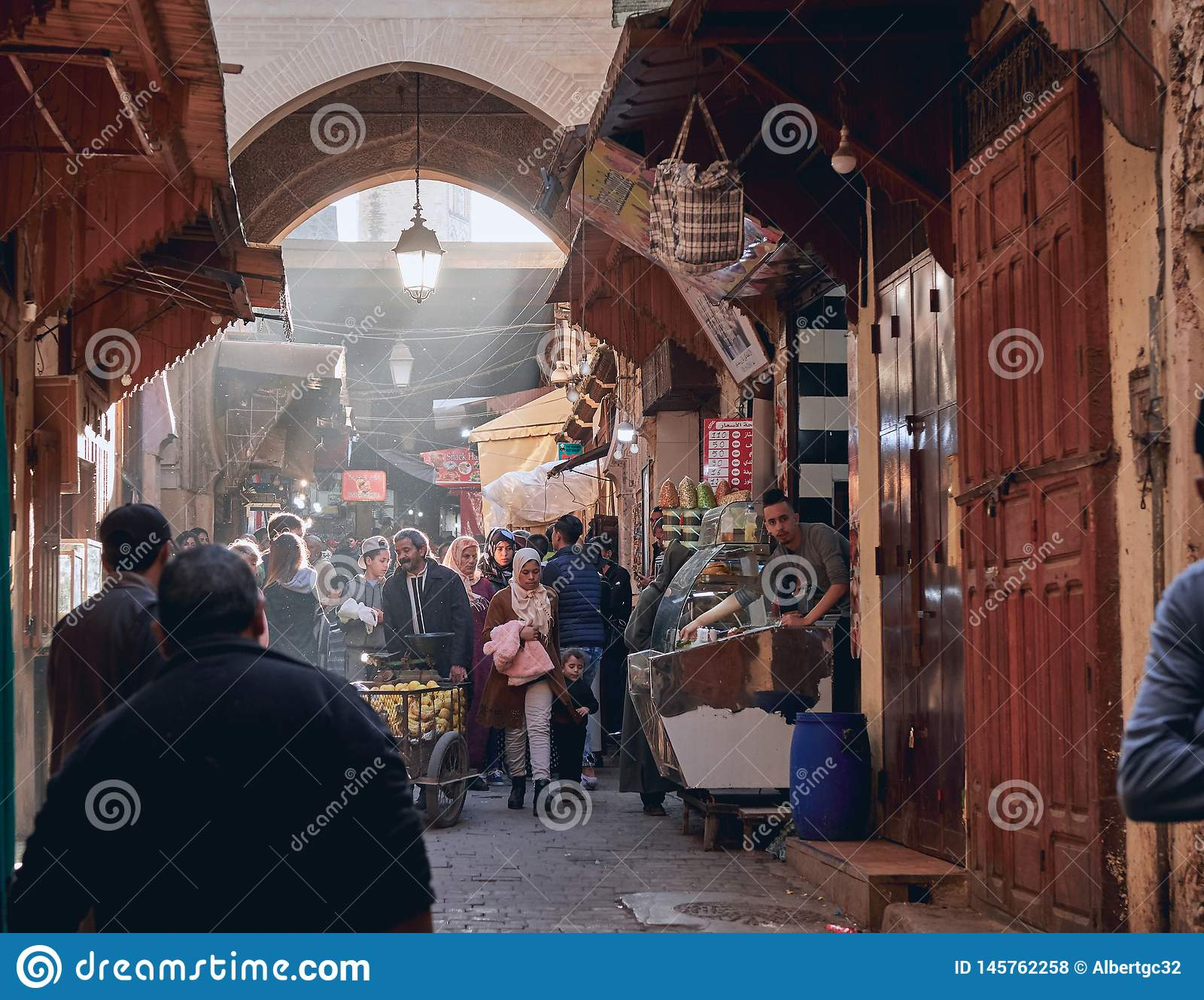 Fez, Morocco - December 07, 2018: Moroccan lady with her daughter walking through a passage of the fez medina with rays of light