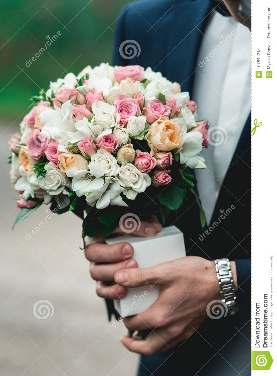 Fiance In A Dark Blue Suit Holds A Wedding Bouquet Made Of White ...