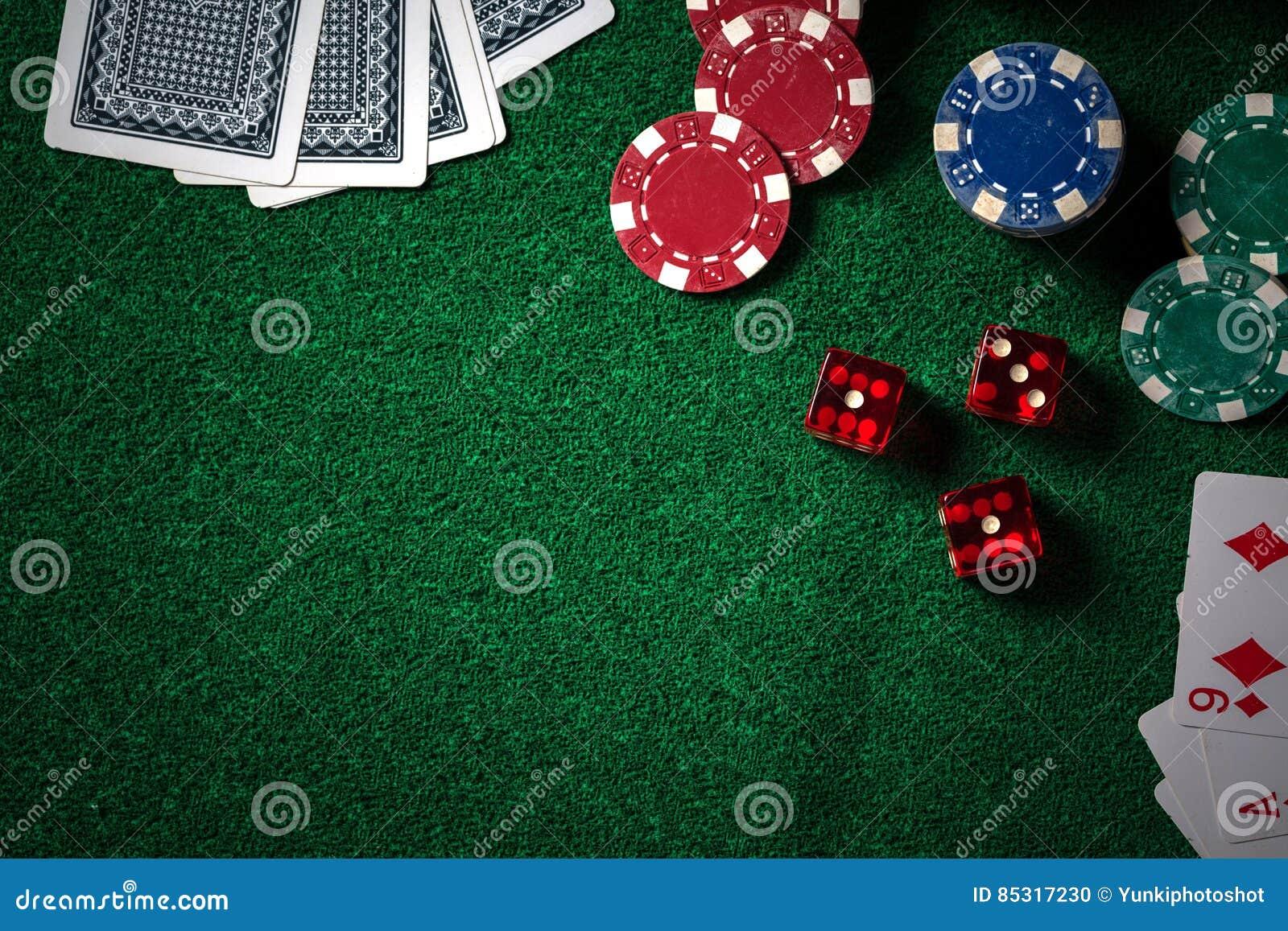 Fichas de póker y tarjetas del juego en la tabla verde del casino con oscuro