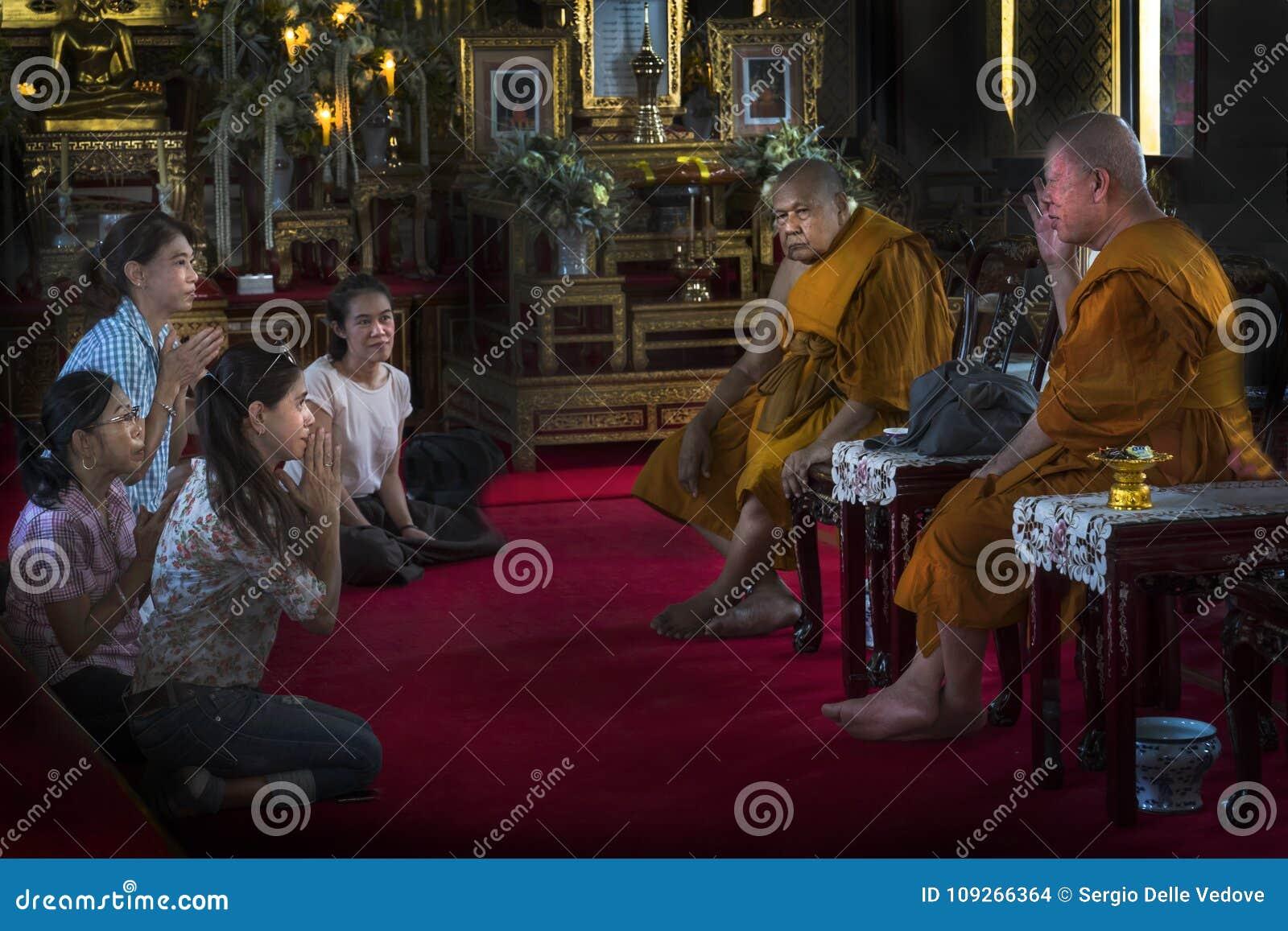 Fiel e monges no templo em Banguecoque