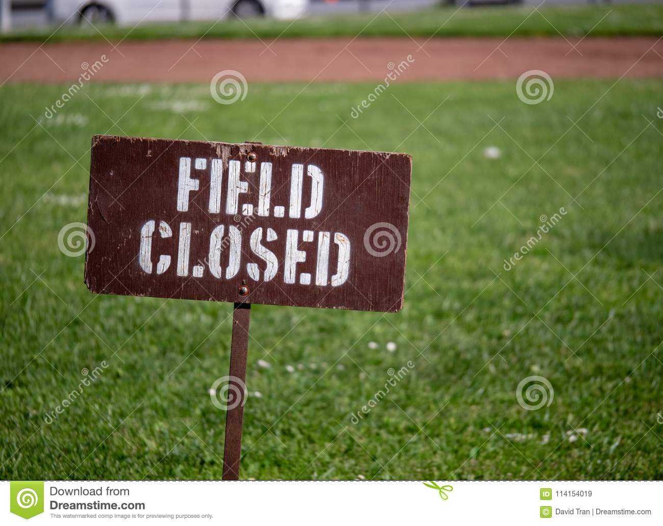 """Field closed"" sign blocking access to a field in a park"