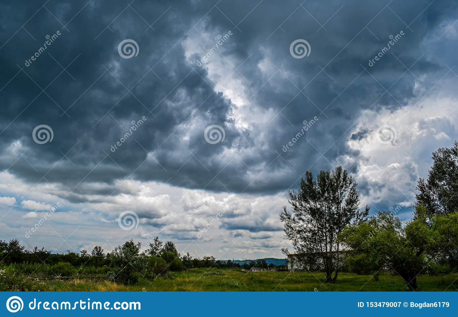 A field of green trees and a sky full of black, threatening clouds. Strong storm begins