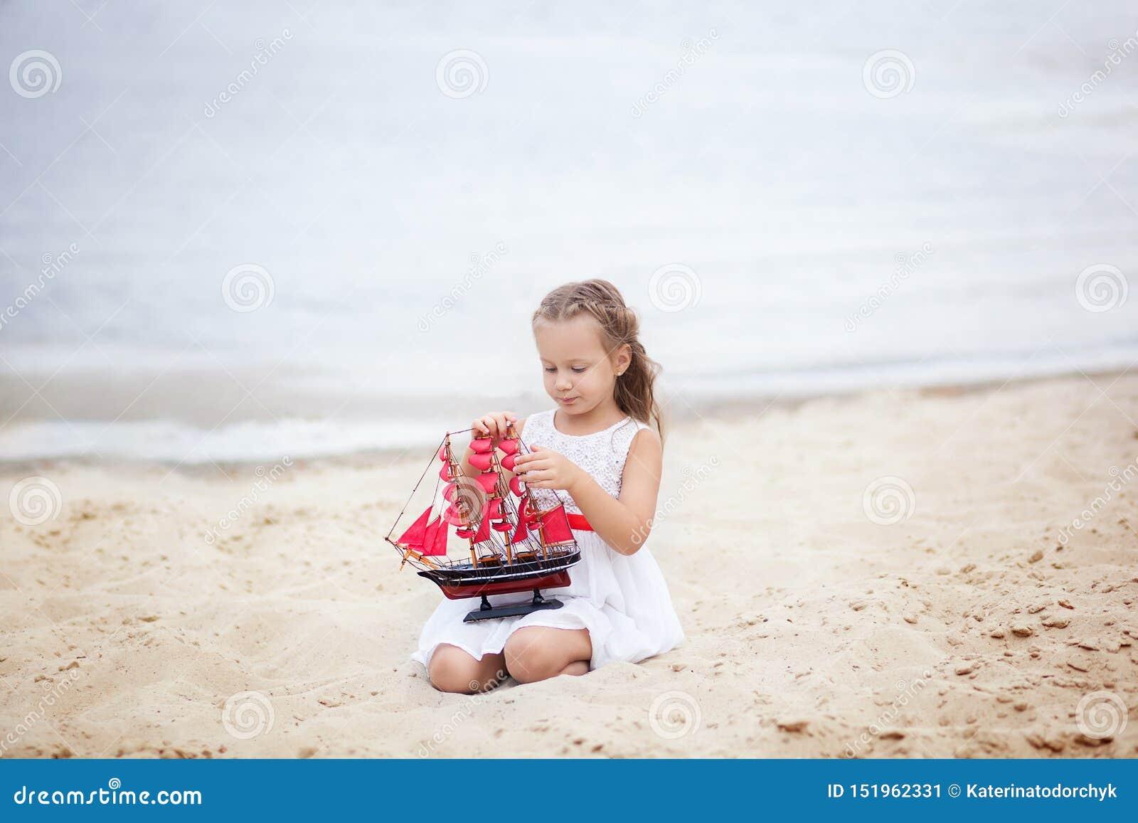 Field treen Bekymmerslös lek för lycklig barndom på den öppna sanden Begreppet av vilar flickan på havet med ett skepp St?ende av