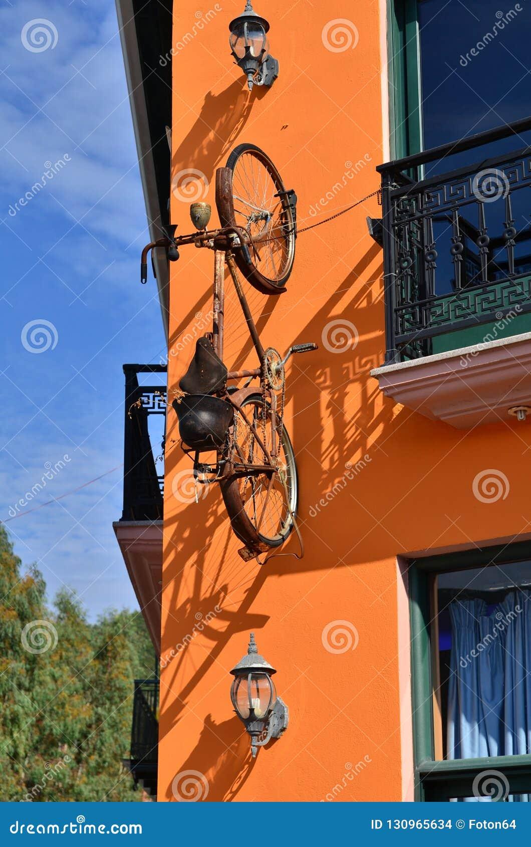 Fiets het hangen op de oranje muur