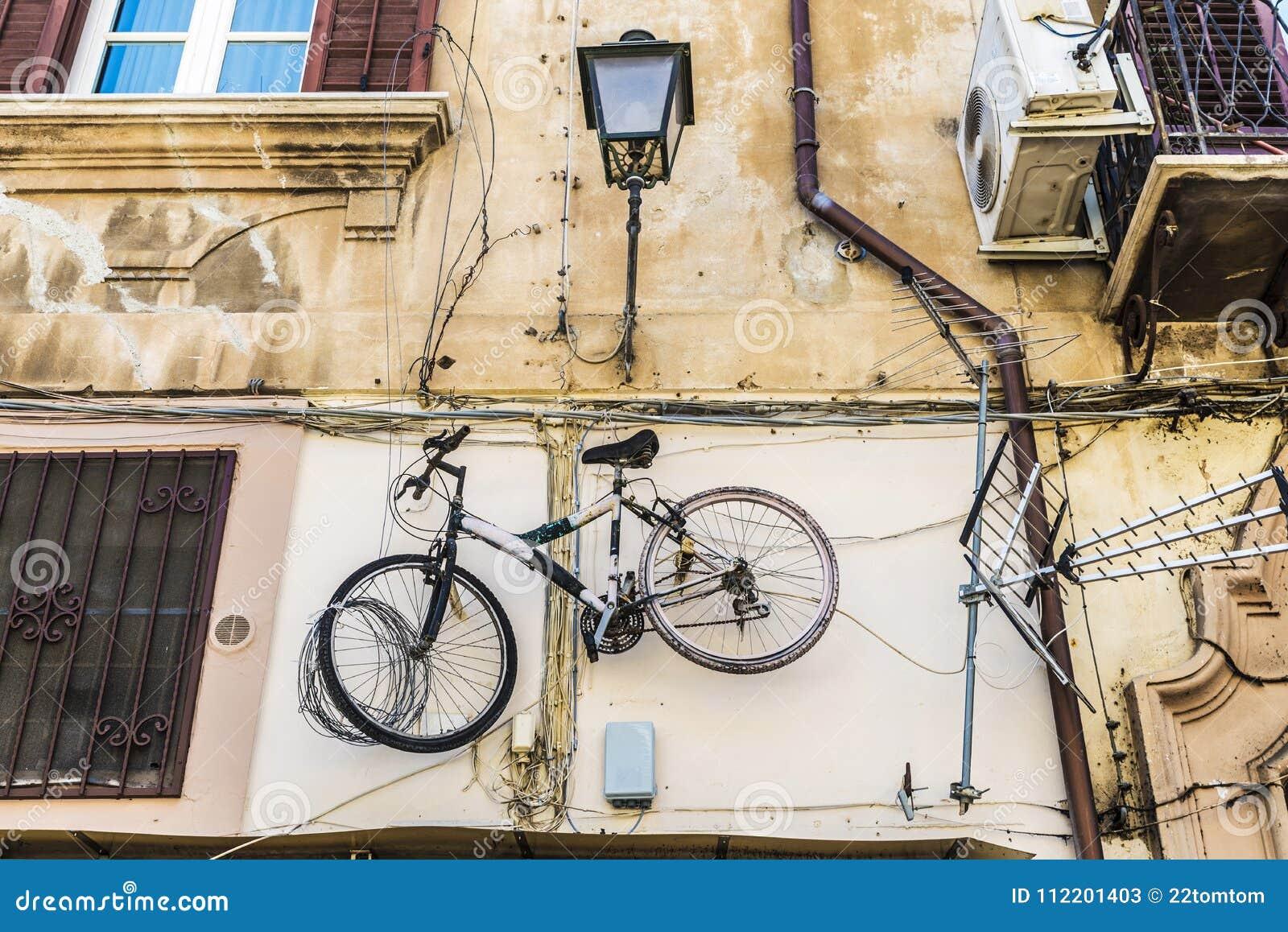 Fiets het hangen op een oude muur in Palermo, Sicilië, Italië
