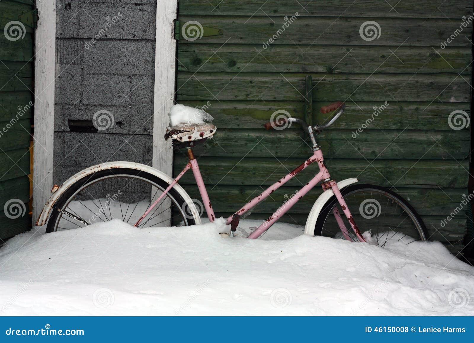 Fiets in Sneeuw door oude loods