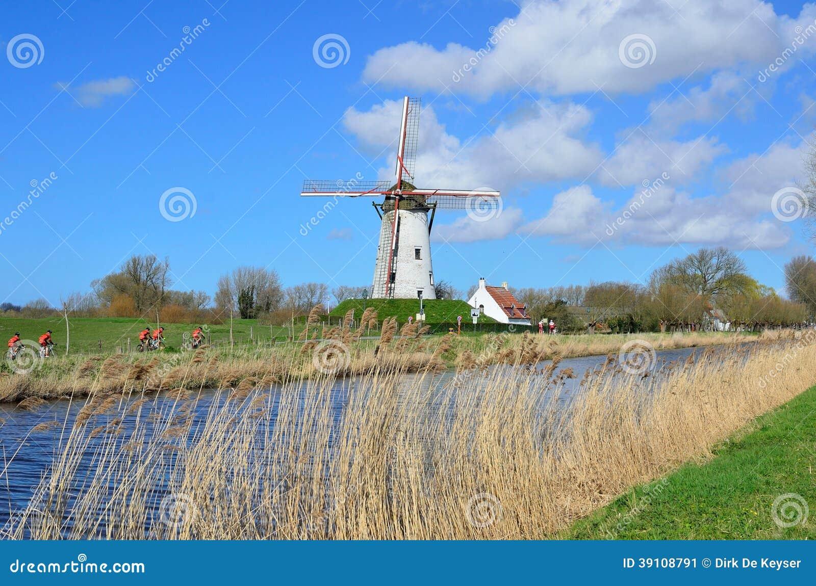 Fietsers die door een oude windmolen in Damme overgaan
