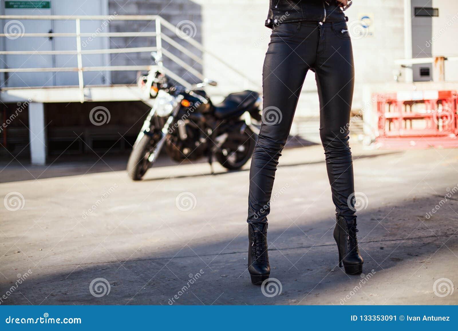 Fietservrouw in leerjasje die zich voor motor bevinden