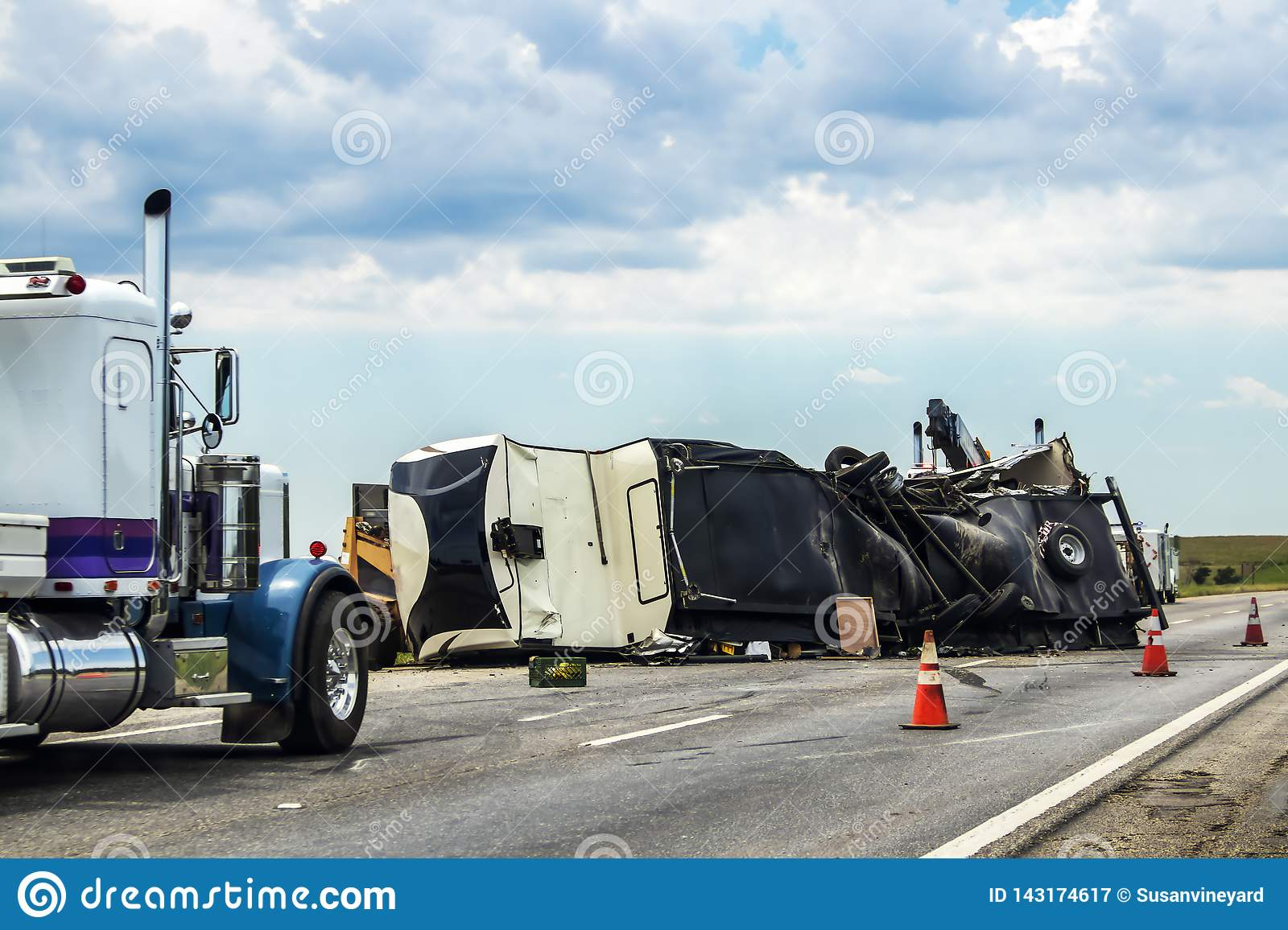 Fifth wheel RV overturned on highway with wench truck trying to get it off the road and two semis parked nearby and traffic cones
