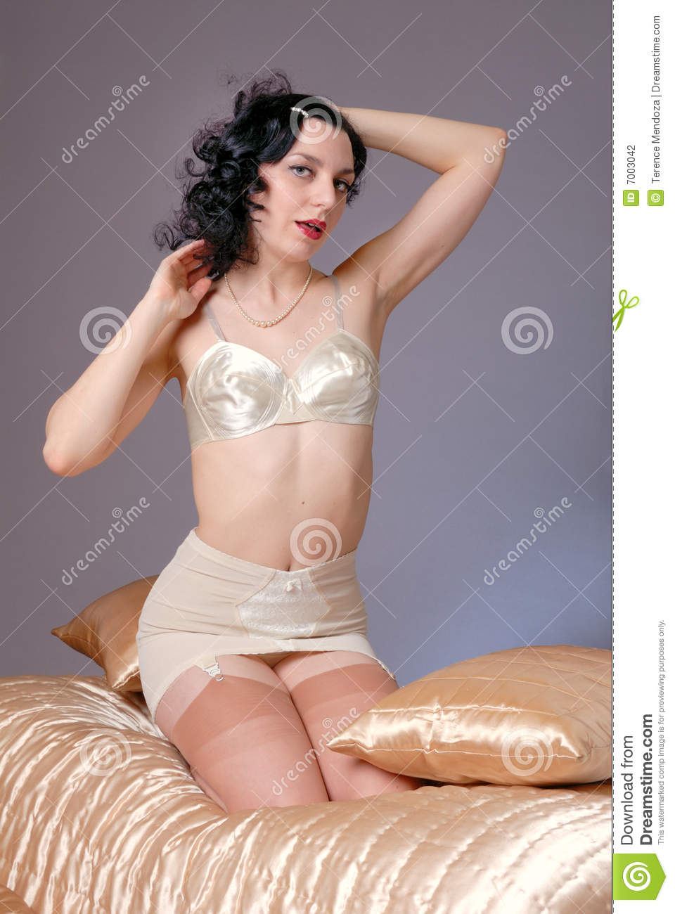 7f934bf09 Retro fifties pin-up attractive girl in vintage satin bra and girdle in  boudoire   bedroom - satin cover pin-up concept