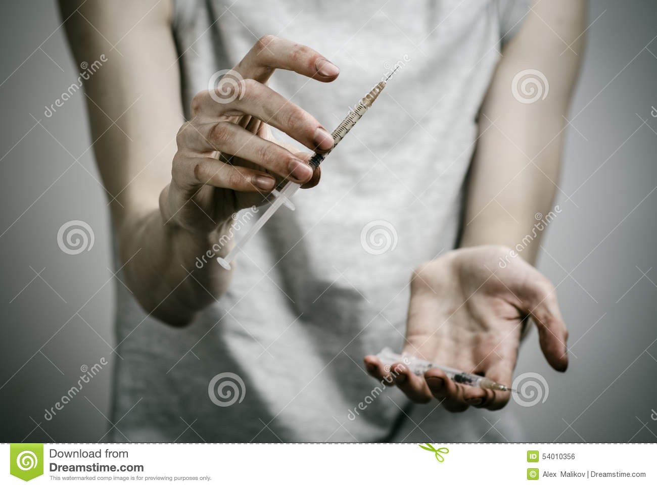The fight against drugs and drug addiction topic: skinny dirty addict holding a syringe with a drug and red heart on a dark