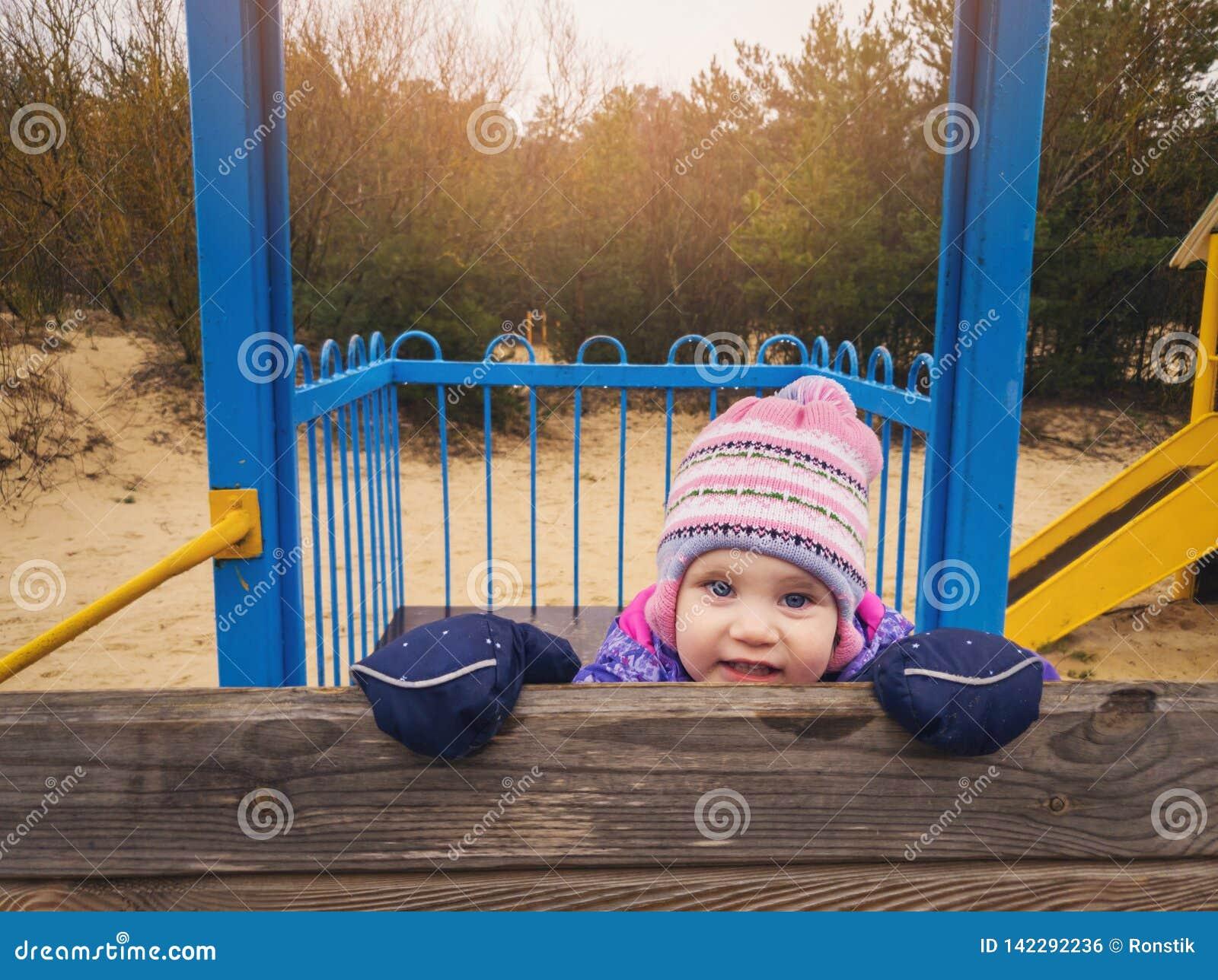 Figlarnie szczęśliwa mała dziewczynka przy boiskiem