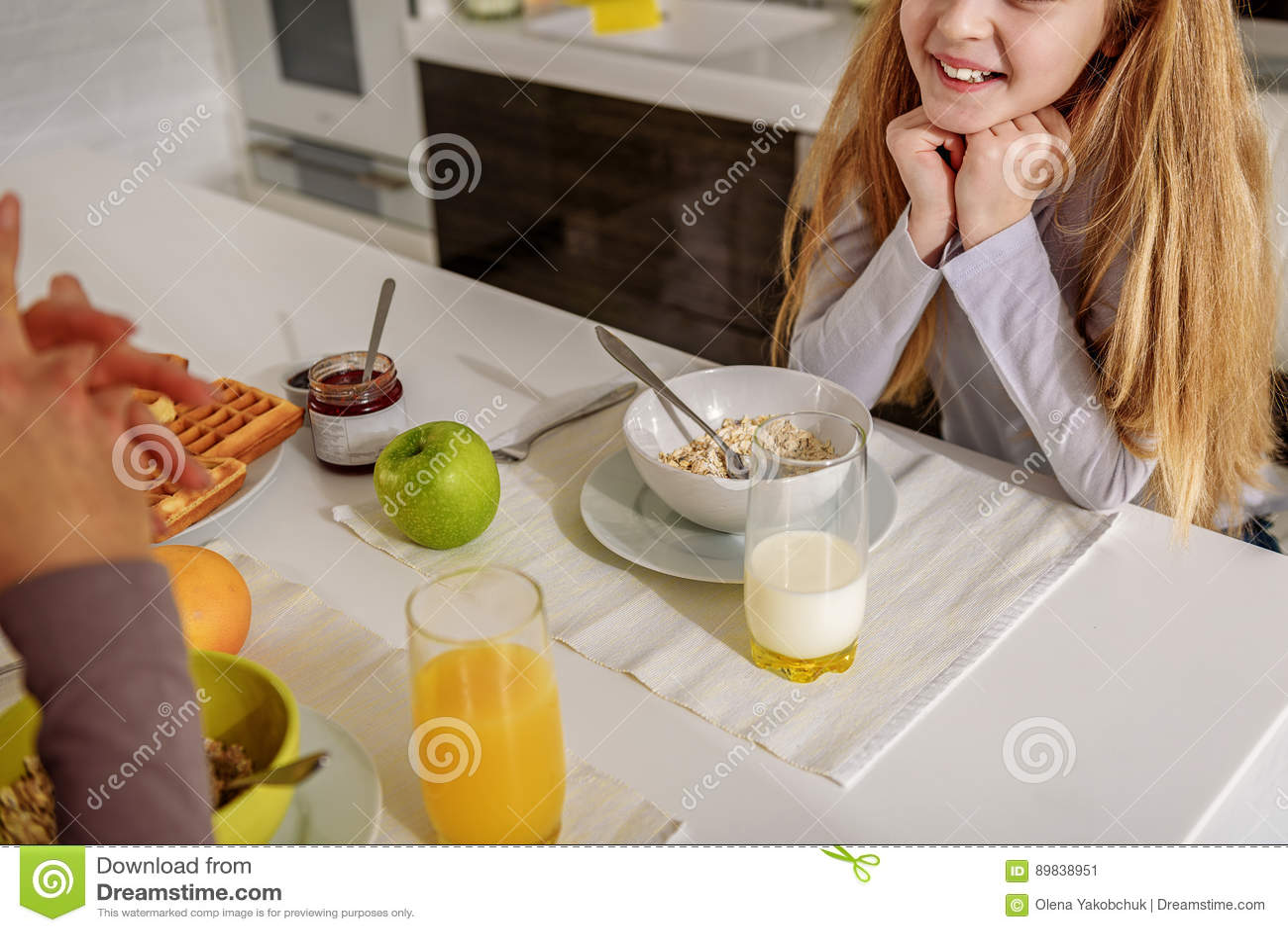 Figlia allegra che gode della conversazione con la mamma in cucina