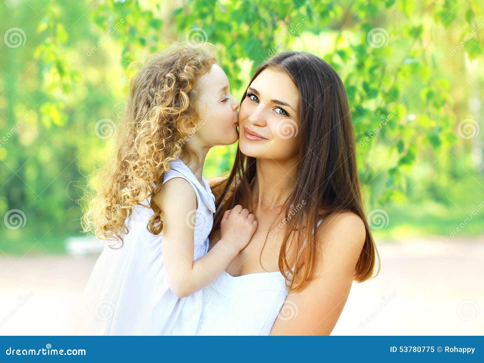 Figlia amorosa che bacia madre, giovane mamma felice e bambino nel giorno di estate soleggiato caldo sulla natura