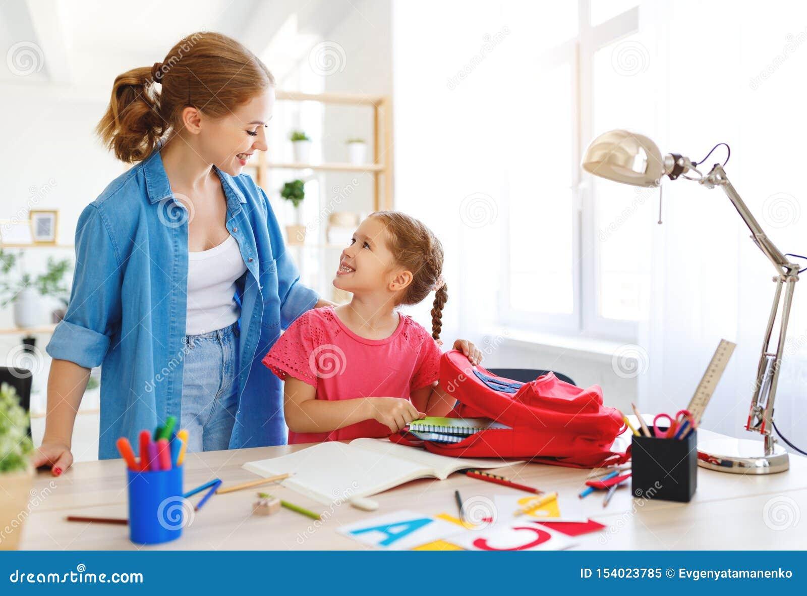 Figlia del bambino e della madre che fa scrittura e lettura di compito