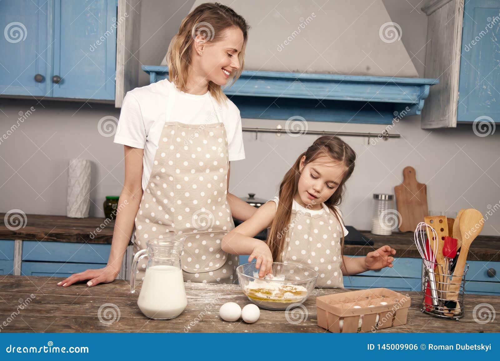 Figlia del bambino e della mamma nella cucina che prepara pasta, biscotti bollenti La mamma insegna a sua figlia ad impastare la