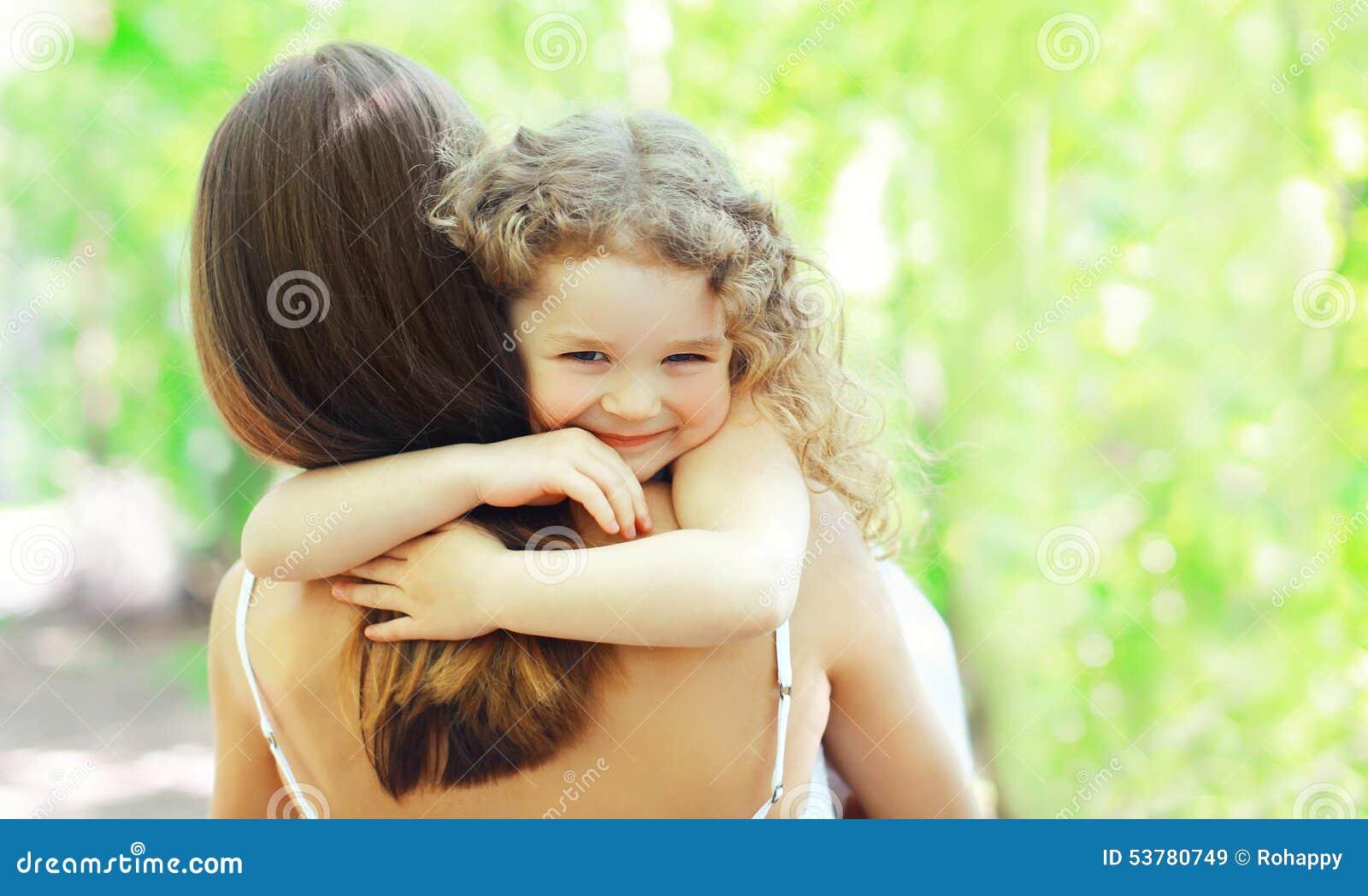Figlia felice che abbraccia madre nel giorno di estate soleggiato caldo sulla natura