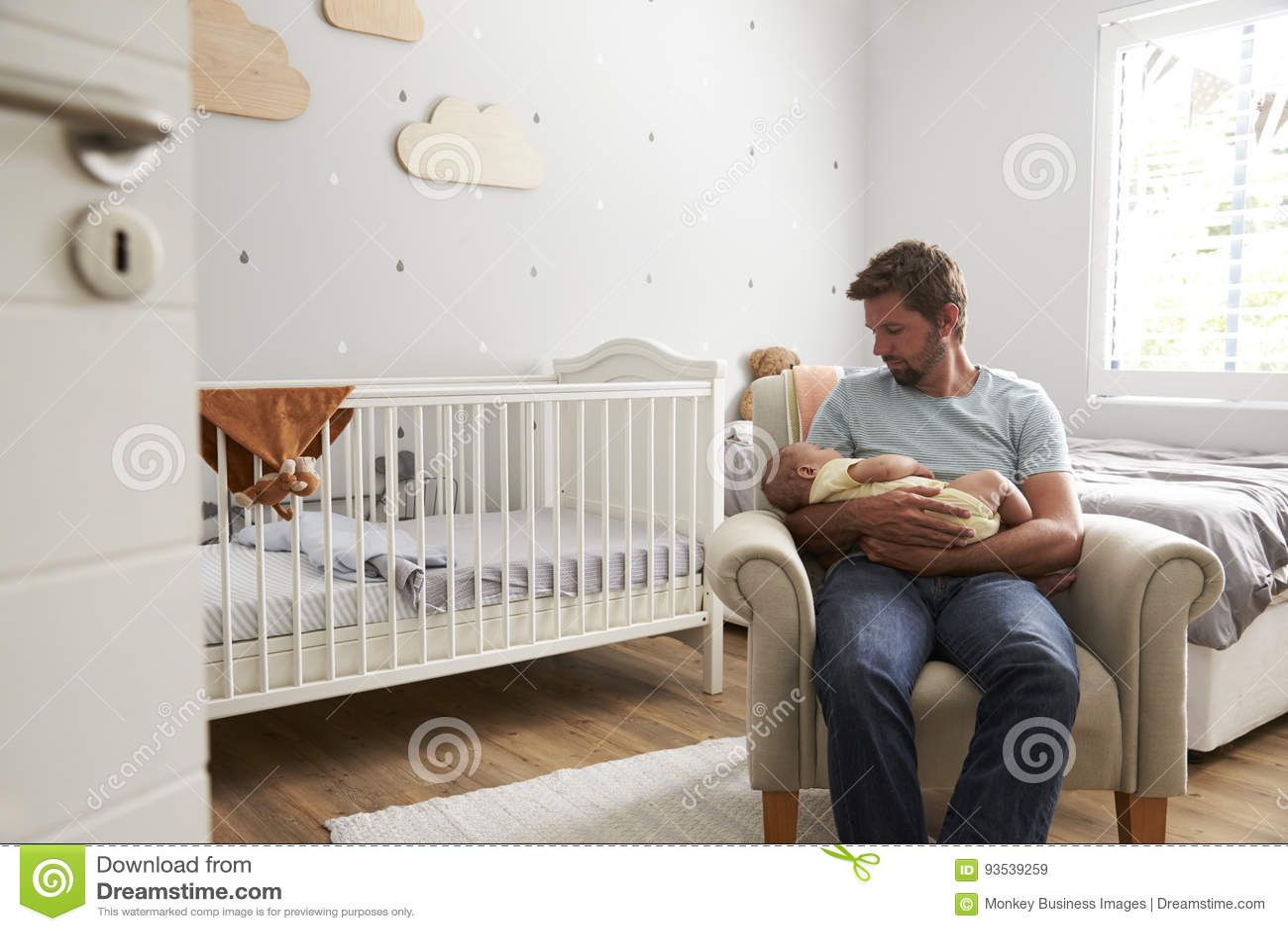 Figlio addormentato del bambino delle tenute della sedia di Sitting In Nursery del padre