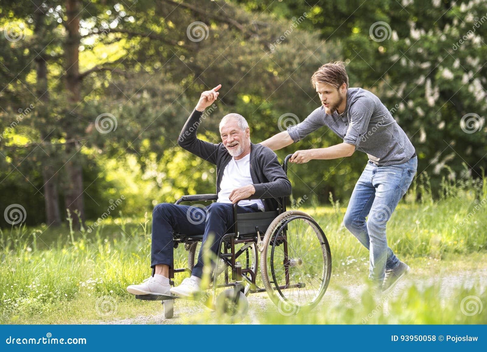 Figlio dei pantaloni a vita bassa che cammina con il padre disabile in sedia a rotelle al parco