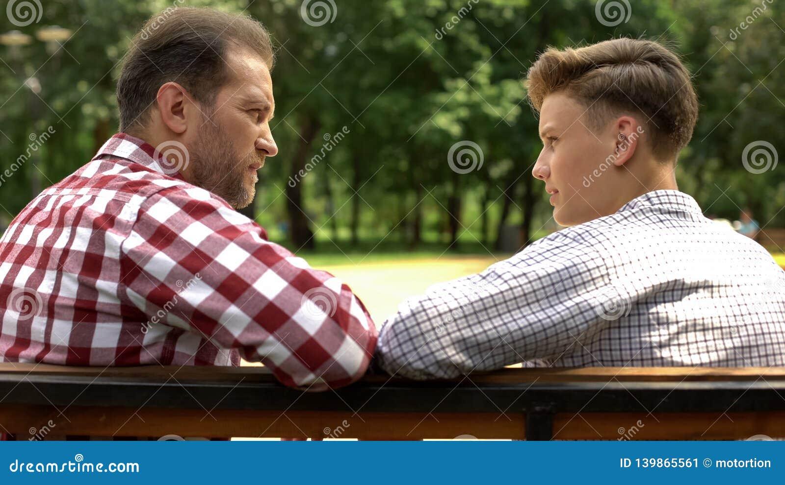 Figlio serio e papà che parlano sul banco in parco, padre che condivide esperienza di vita