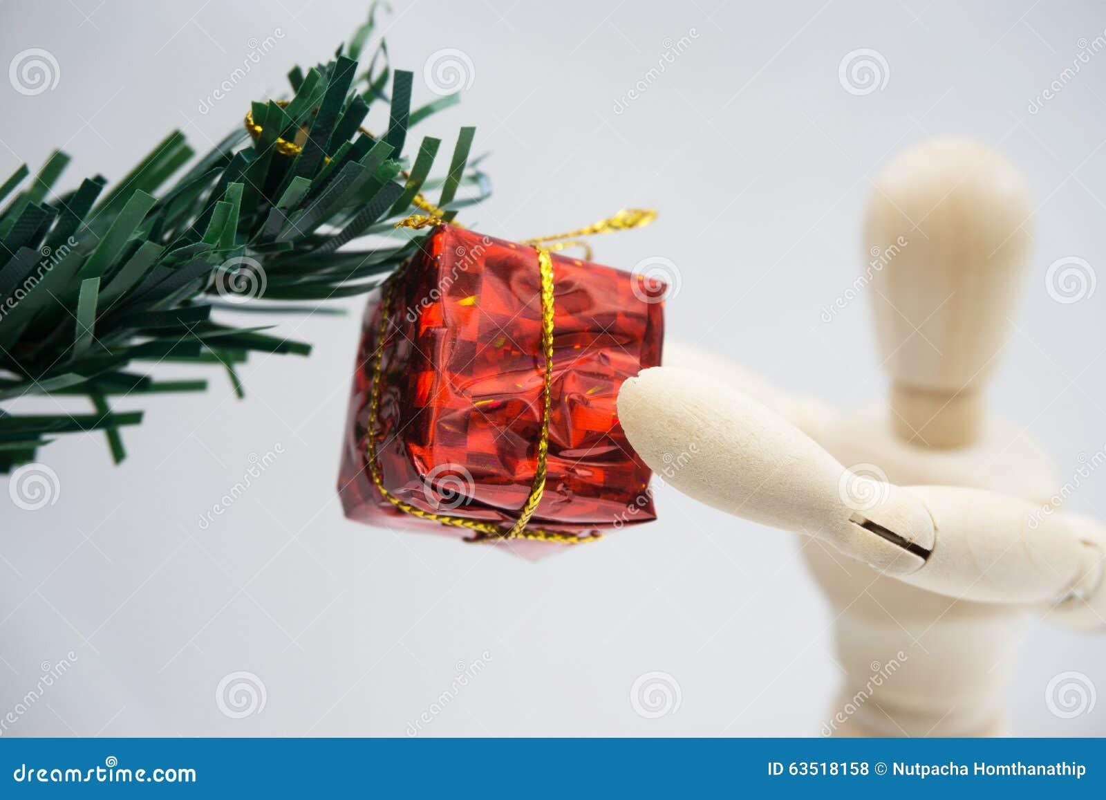 Foto de Stock: Figura de madeira boneca e caixa de presente vermelha  #AA4321 1300x957