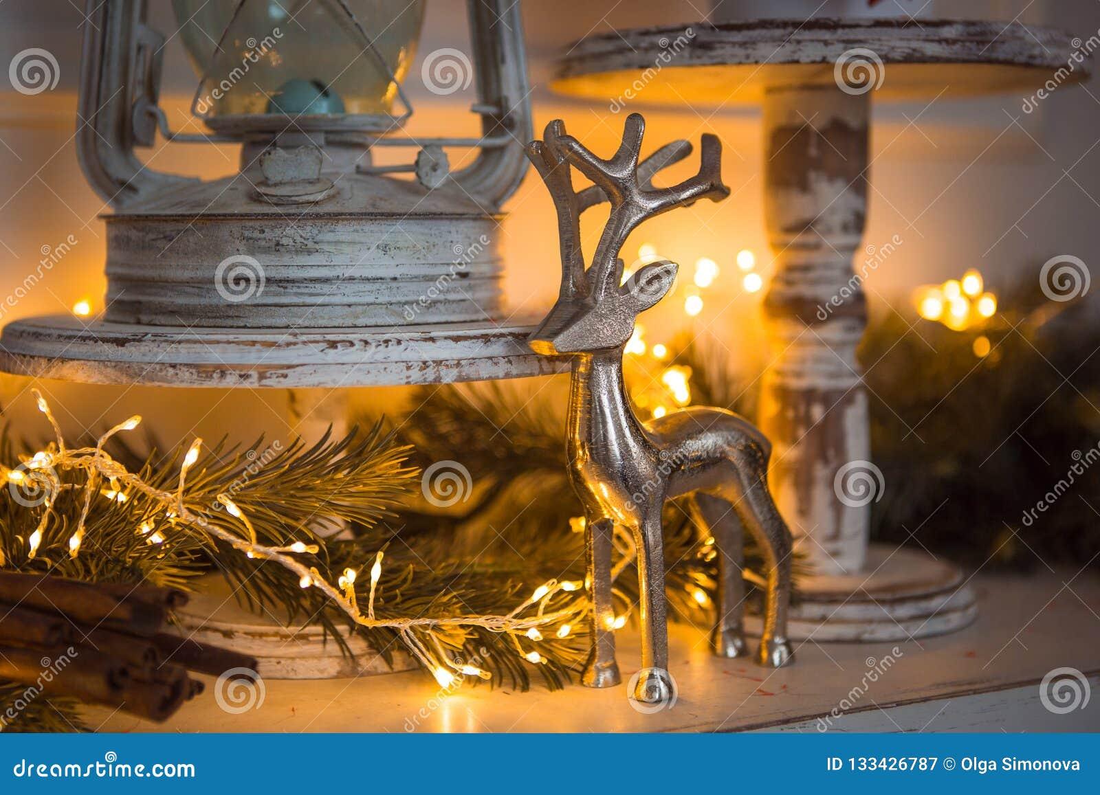 Figura de plata de la decoración de la Navidad de un ciervo, palillos de canela en la guirnalda festiva de las luces amarilla