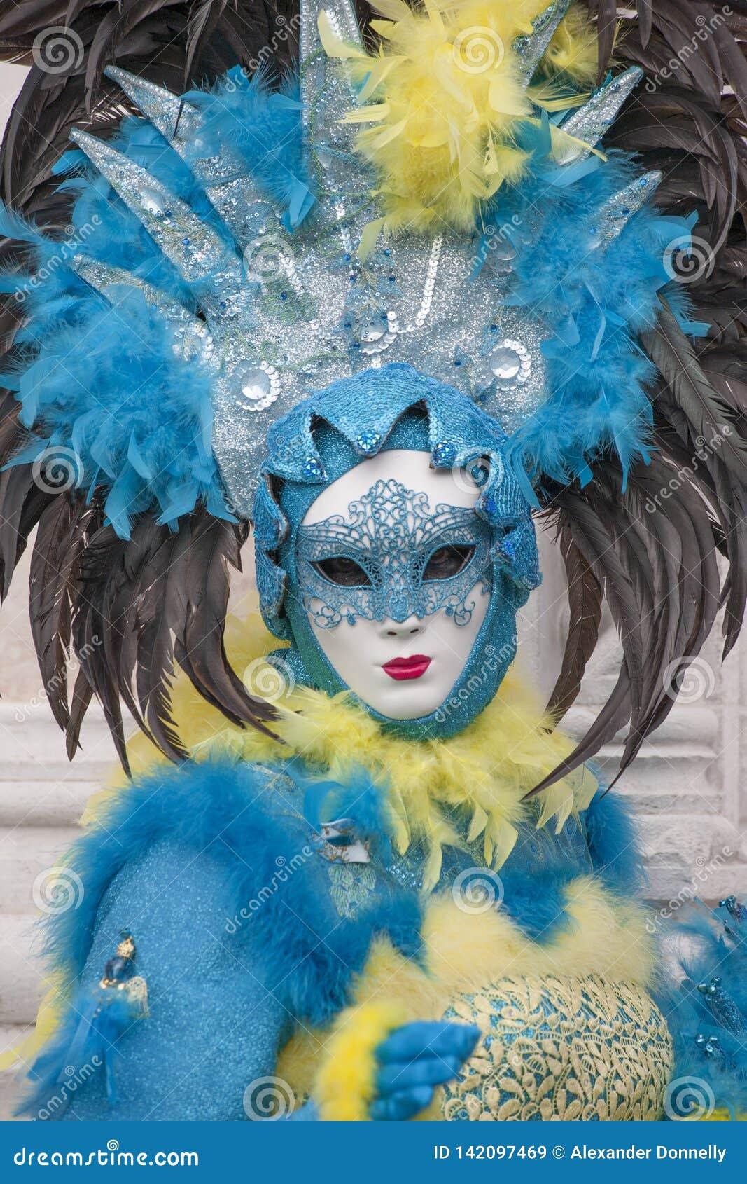 Figura do carnaval de Veneza que veste o traje azul, amarelo e preto colorido e a máscara venetian Veneza Itália