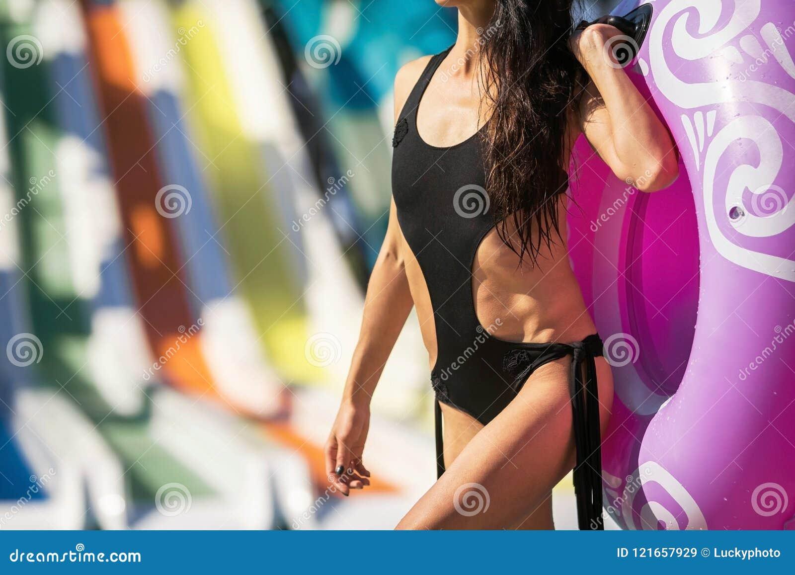 Figura perfeita magro da mulher com anel da nadada perto da associação e das corrediças