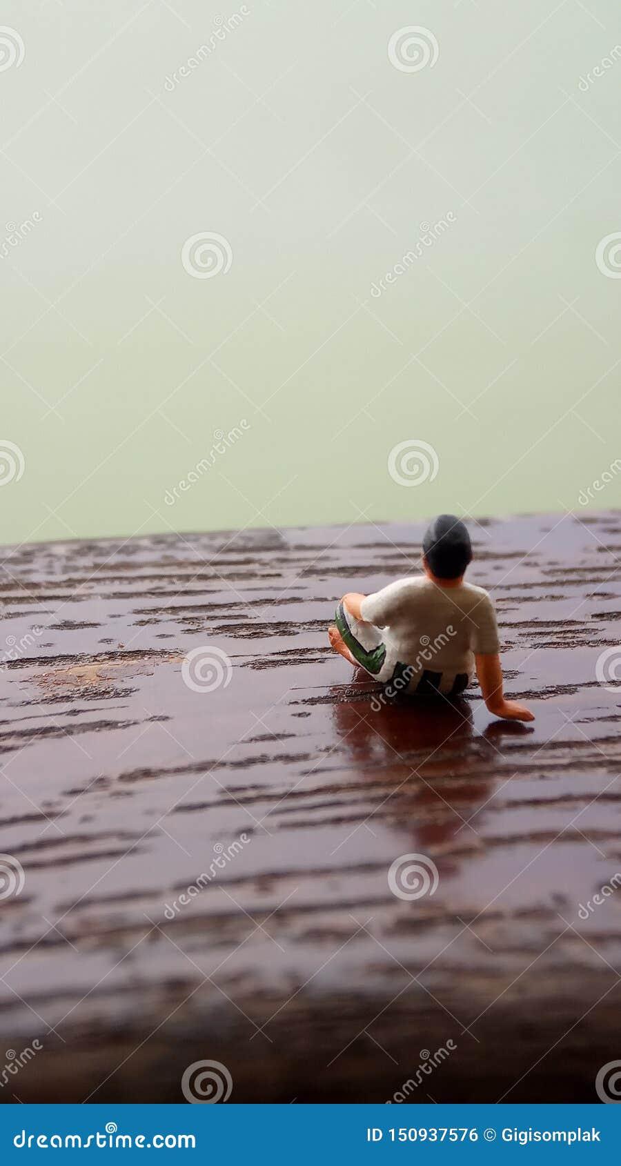 Figura simple, mini viejo hombre del juguete sentarse en el balcón de madera del rasguño en el lado del río con la copia o espaci