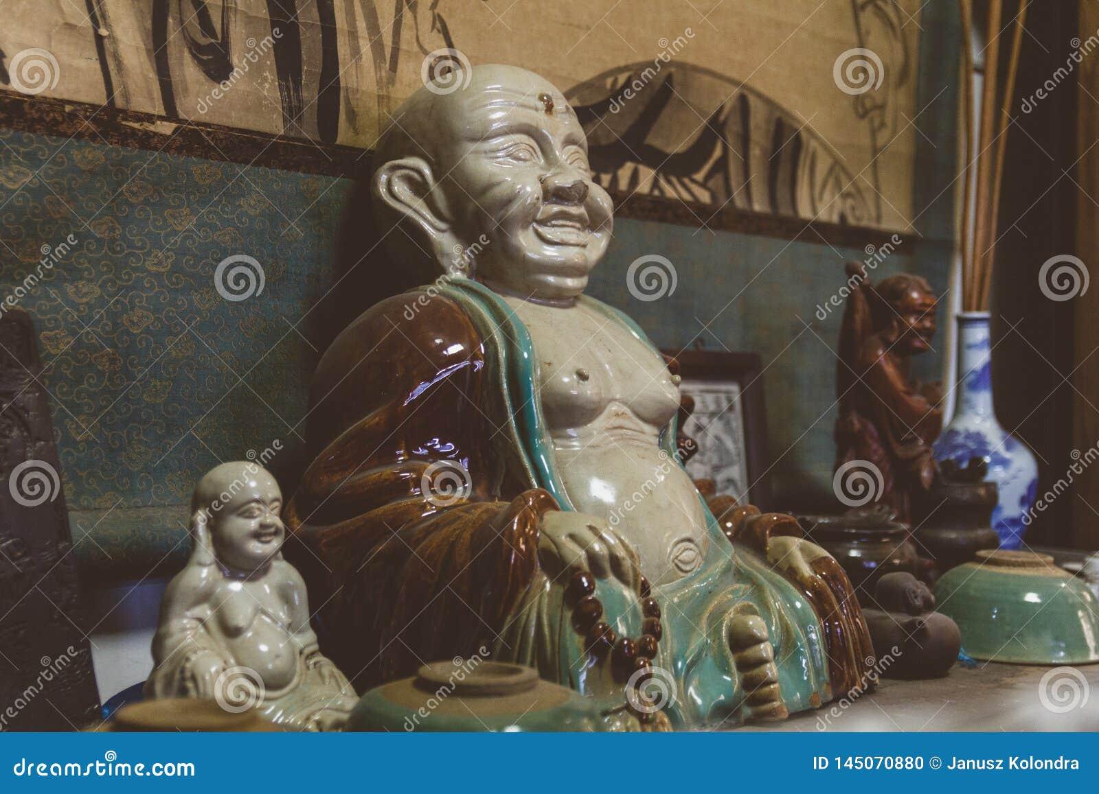 Figuras da Buda da porcelana na loja chinesa antiga