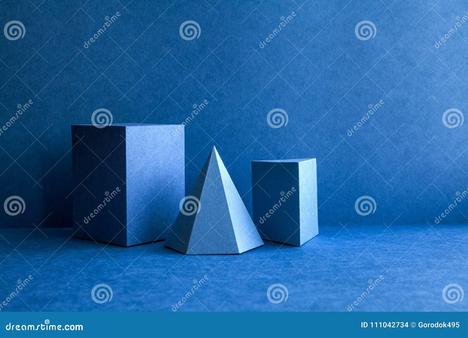 Figuras geométricas ainda composição da vida O cubo retangular do tetraedro tridimensional da pirâmide de prisma objeta no azul