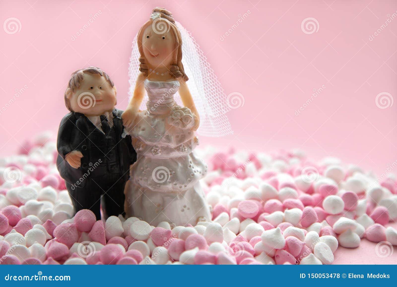 Figuras miniatura de los cónyuges, novia y novio, colocándose en un rosa y un blanco del mini-merengue en un fondo rosado Miniatu