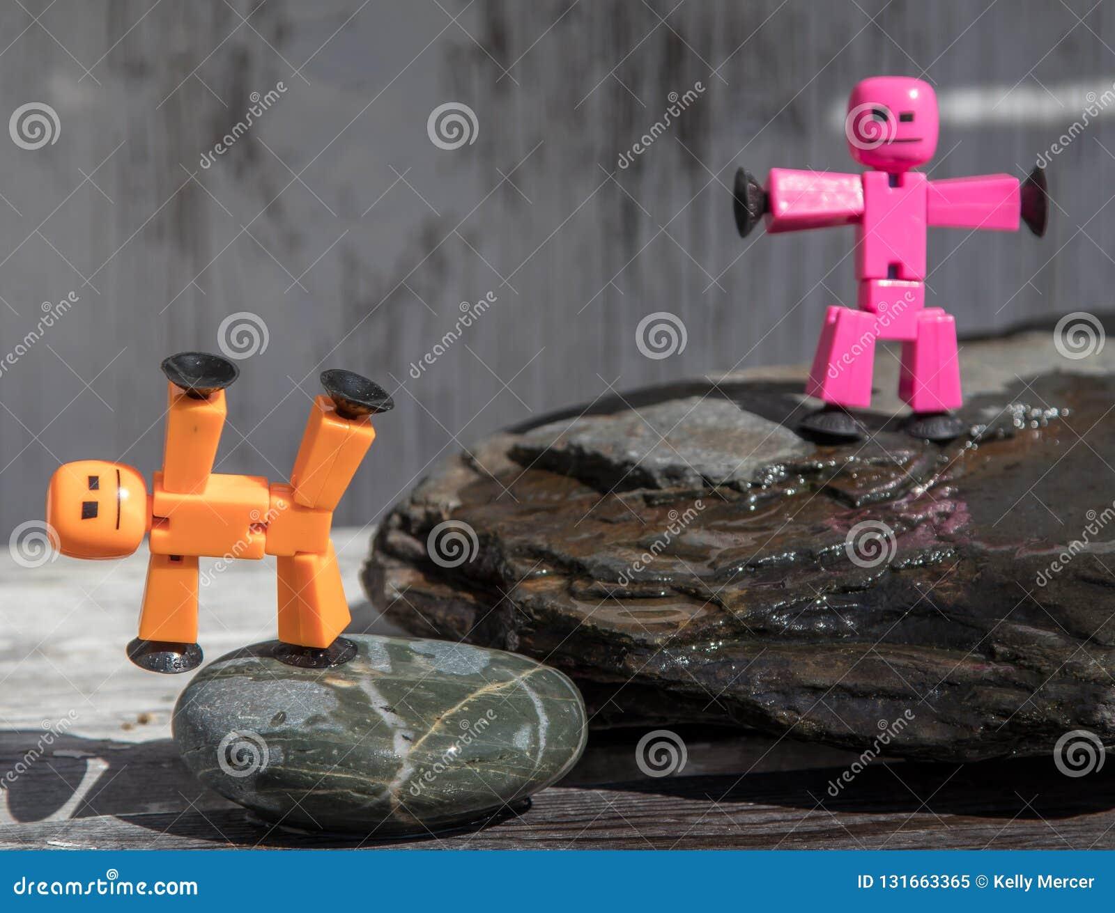 Figuras plásticas del palillo planteadas en rocas mojadas