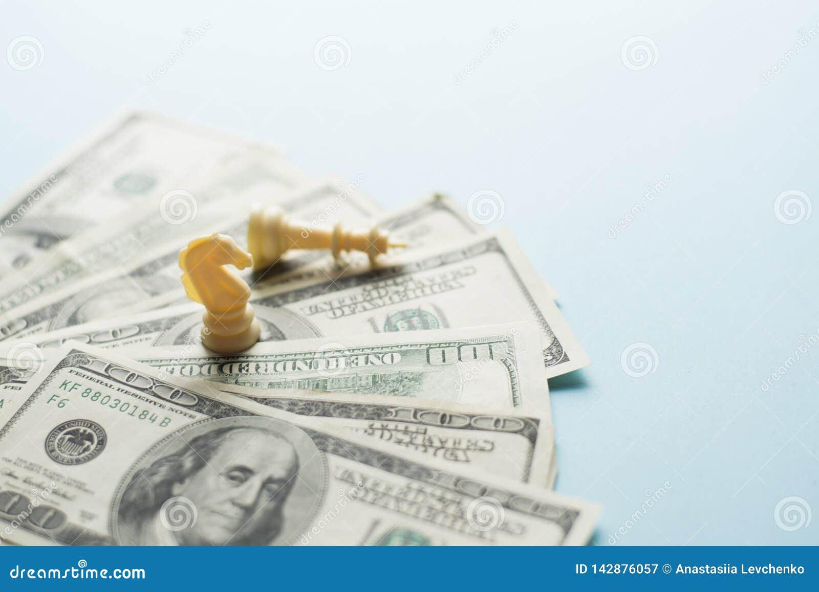 Figuras y dólares americanos del juego de ajedrez en fondo azul con el foco selectivo, planificación de la estrategia empresarial