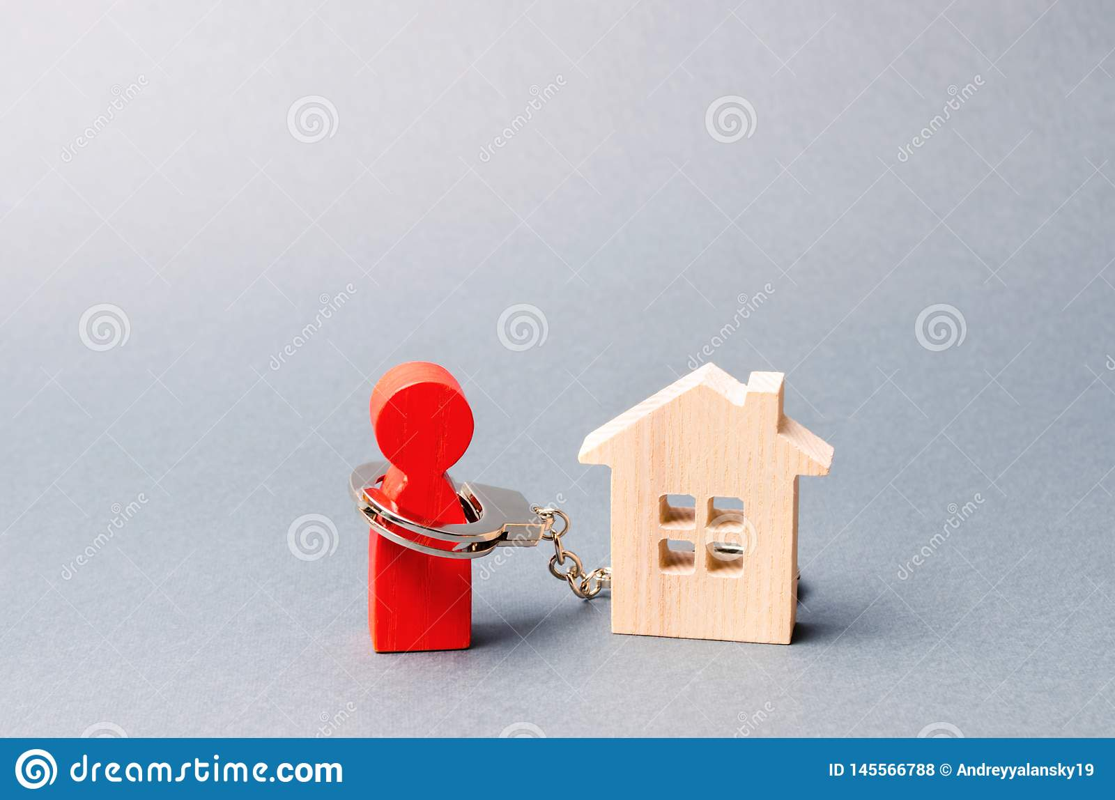 The figure of a man is handcuffed to a wooden house. Impossibility of paying interest rates on mortgages and repayment of loans.