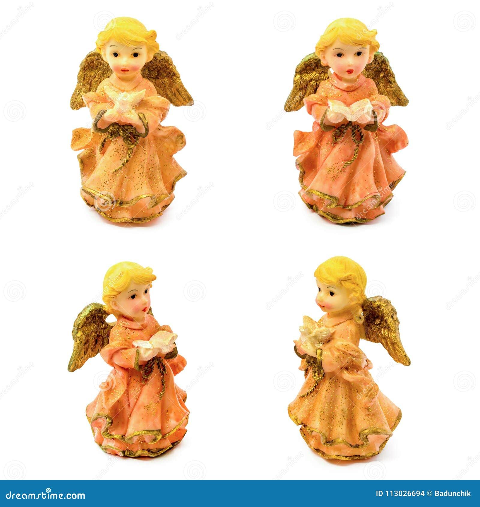 Figurilla de los ángeles de la porcelana con el libro y la paloma aislados en el fondo blanco