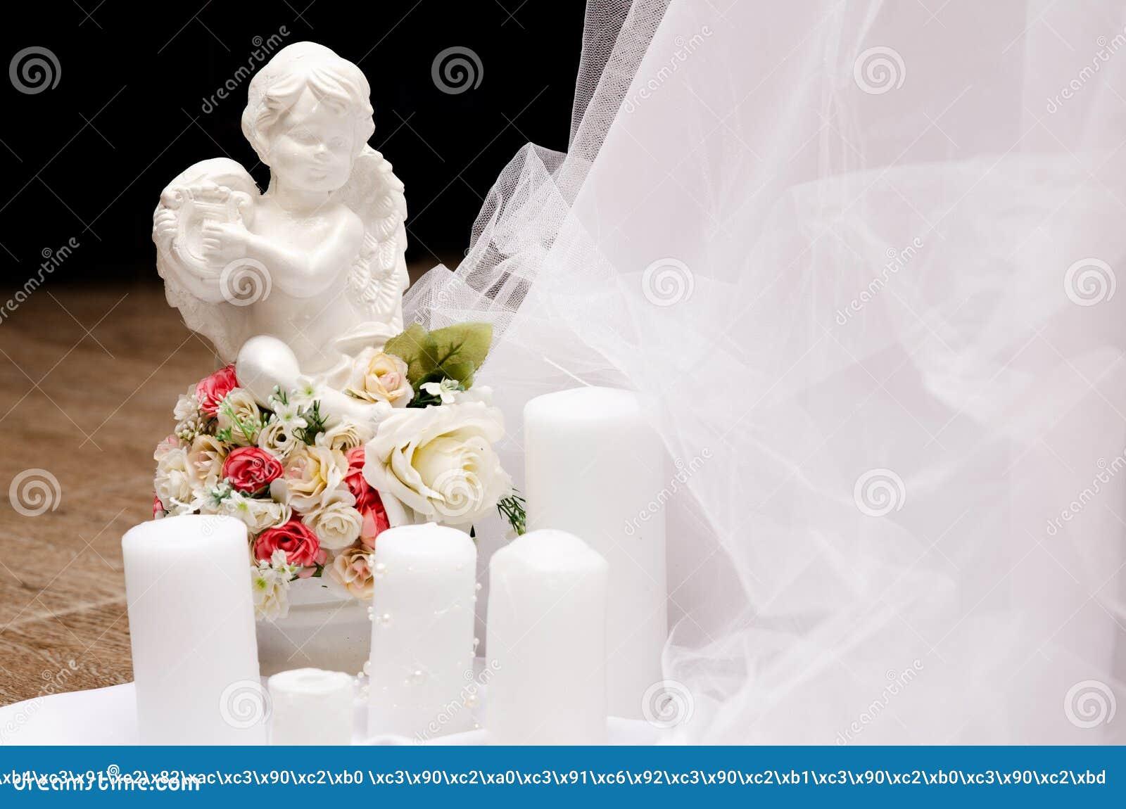 Figurina di angelo con le candele e le rose di nozze