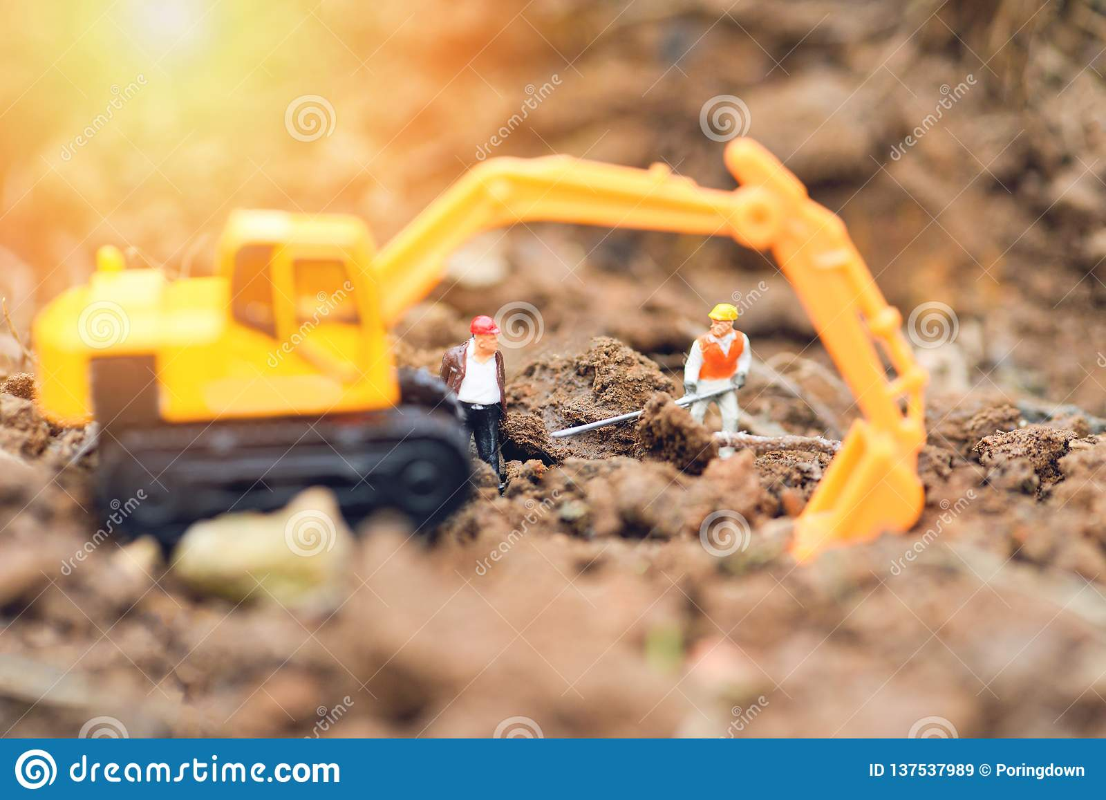 Figurines рабочий-строителя работая выкапывая земная почва с экскаватором Backhoe