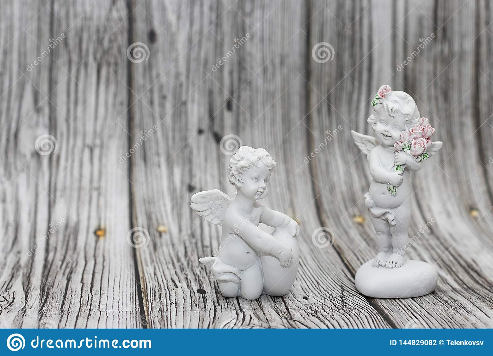 Figurines Of Angels On A Wooden Background A Boy With A Heart And A