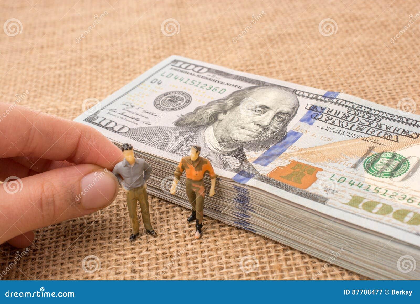 Figurines d hommes près du paquet du billet de banque de dollar US
