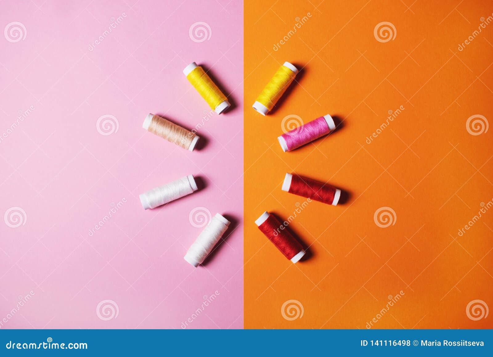 Fije de hilos de coser coloridos en fondo brillante