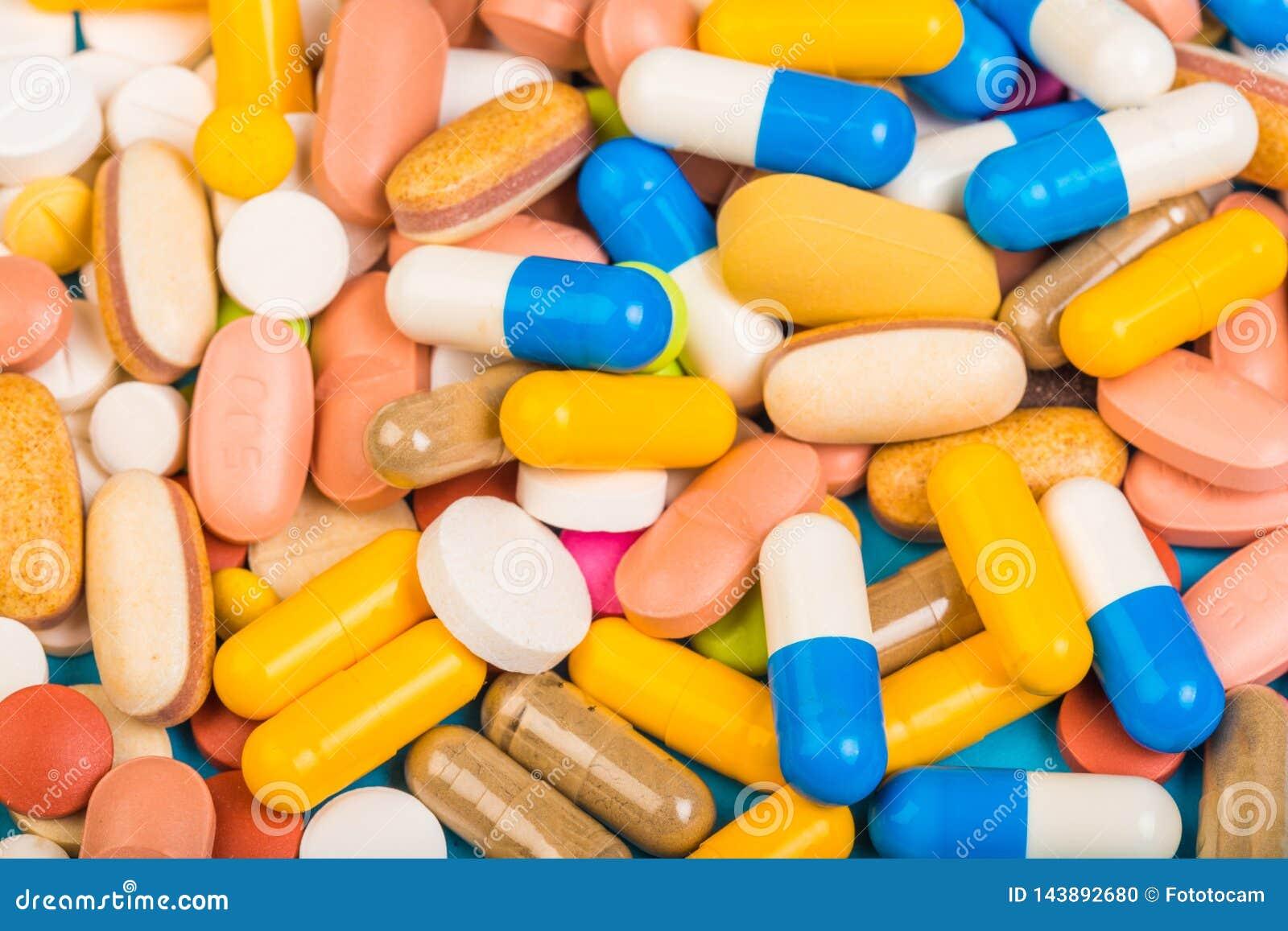 Fije de tabletas y de cápsulas multicoloras en un fondo azul