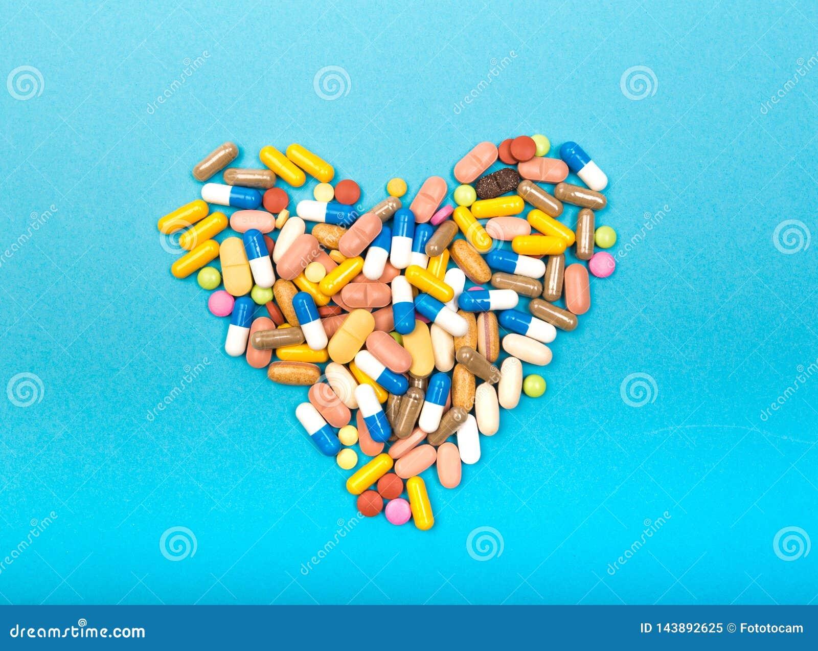 Fije de tabletas y de cápsulas multicoloras en una forma azul del corazón del fondo