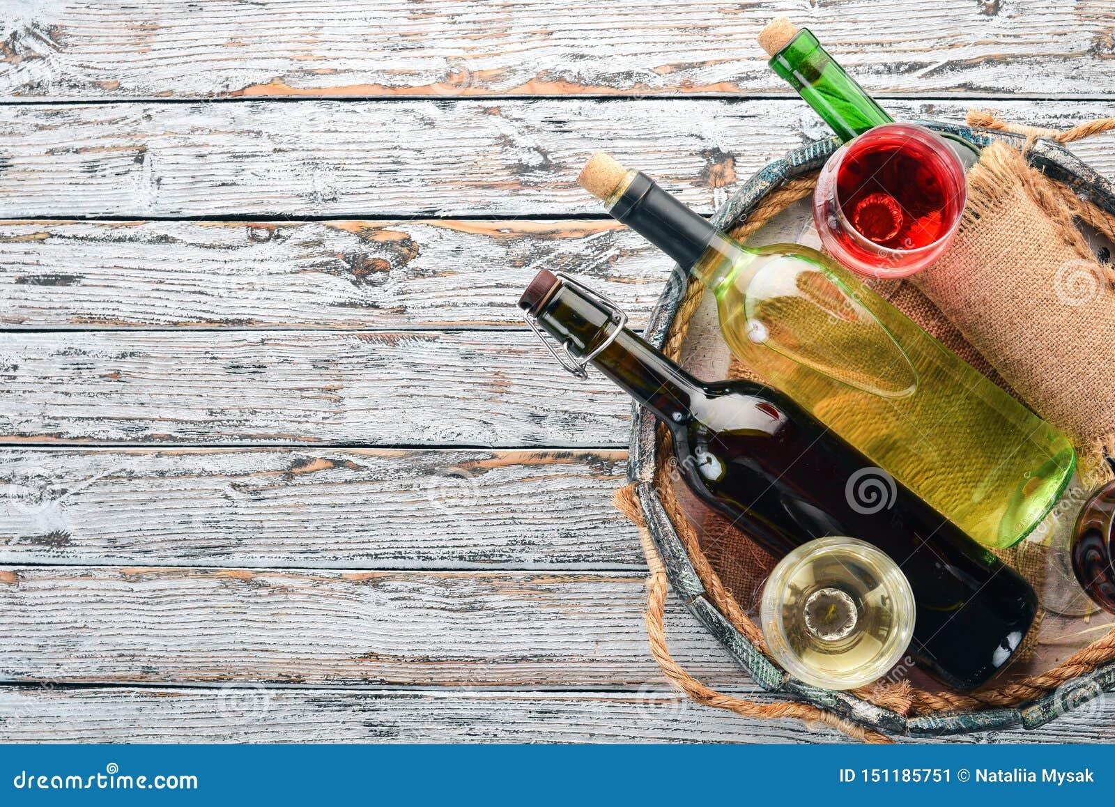 Fije del vino blanco rojo y en botellas y vidrios uva En un fondo de madera blanco Espacio libre para el texto