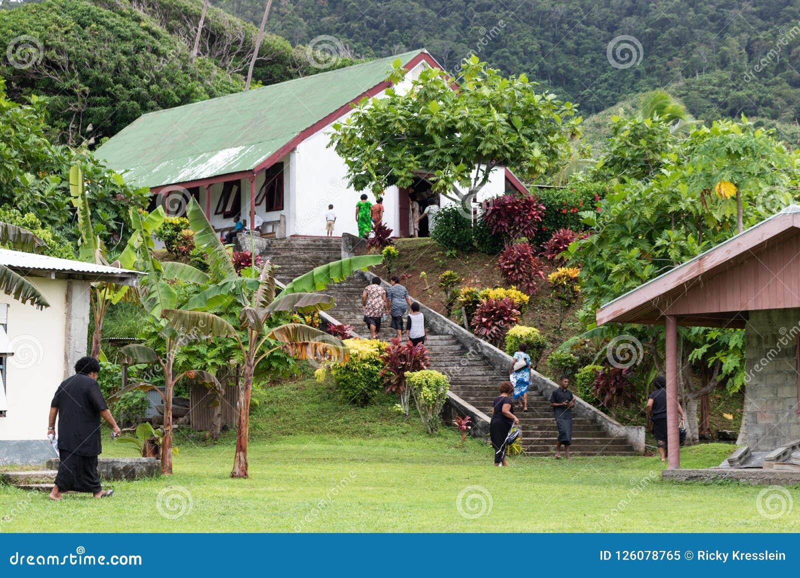 Fijians que caminan encima de las escaleras a la iglesia en pueblo