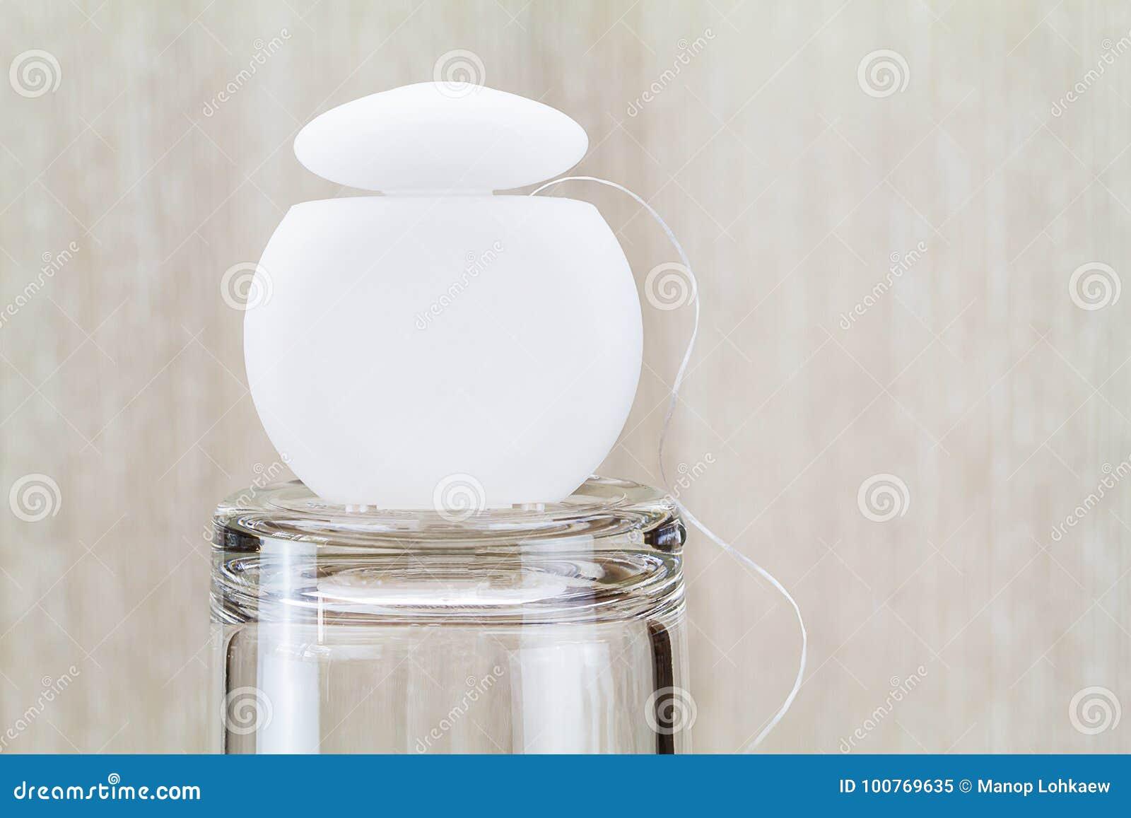 Fil dentaire sur le verre dans la salle de bains sur le fond en bois brouillé