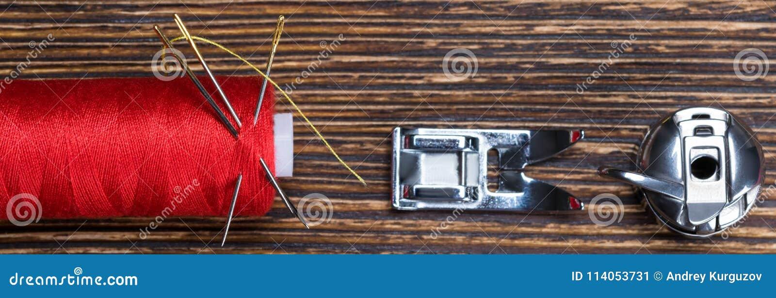 Fil rouge de bobine sur un fond en bois, avec un ensemble de pièces de rechange pour une machine à coudre