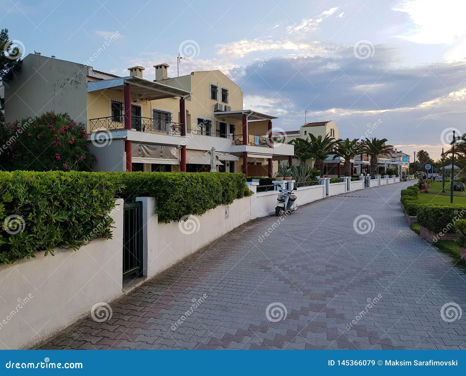 Fila de casas modernas con la cerca del seto y el camino de piedra hermoso